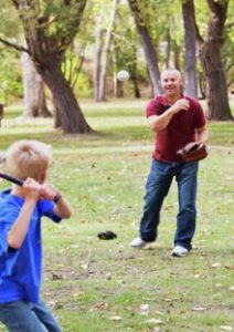 photo of young person and volunteer playing baseball